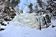 Happy girl standing  above frozen waterfall Royalty Free Stock Photo