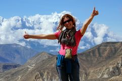 Happy girl is standing, arms outstretched, against the backdrop of the Annapurna massif. royalty free stock photos