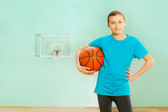 Happy girl standing with basket ball in gym. Portrait of happy 12 years old girl, basketball player, standing with ball in sports hall Stock Photography