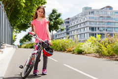 Happy girl standing with bike on cycle path Royalty Free Stock Photo