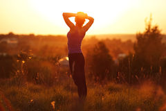 Happy girl standing in a field. At sunset Stock Photos