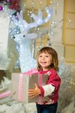 A happy girl is standing with a gift in her hands against the backdrop of a New Year`s deer. Stock Photos