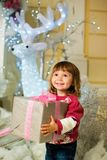 A happy girl is standing with a gift in her hands against the backdrop of a New Year`s deer. Royalty Free Stock Images