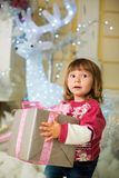 A happy girl is standing with a gift in her hands against the backdrop of a New Year`s deer. Royalty Free Stock Image