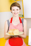 Smiling woman holding fresh loaf of homemade bread Stock Image