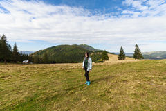 Happy girl standing on a mountain plain Royalty Free Stock Image