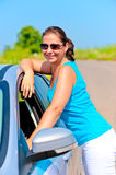 Happy girl standing near her car on the road Stock Image