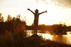 Happy girl standing on a rock at sunset Royalty Free Stock Image