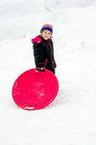 Happy girl standing in the snow with a saucer sled Stock Image