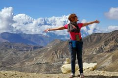 Happy girl standing spread hers arms wide, against the backdrop of the Himalayan mountains. royalty free stock image