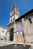 Happy girl standing on square near historic building Stock Photo