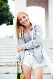 Happy girl standing on stairs with skateboard Stock Image