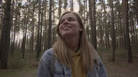 Happy girl standing in the sunny forest and smile. Young female hipster enjoy traveling outdoor standing in forest and smiling by looking around. The sunset stock footage