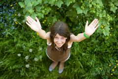 The happy girl stands on a green grass Royalty Free Stock Photo