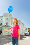 Happy girl stands on street with blue balloon Royalty Free Stock Image