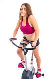 Happy girl on stationary bicycle Royalty Free Stock Image