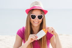 Happy girl in straw hat and sunglasses with sun lotion, sun protection on beach Royalty Free Stock Photo