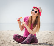 Happy girl in straw hat and sunglasses with sun lotion, sun protection on beach Stock Images