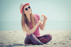 Happy girl in straw hat and sunglasses with sun lotion, sun protection on beach Stock Image