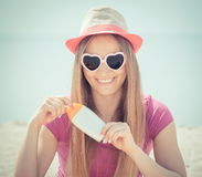 Happy girl in straw hat and sunglasses with sun lotion, sun protection on beach Stock Photos