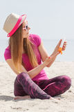Happy girl in straw hat and sunglasses using sun lotion, sun protection on beach Royalty Free Stock Photos
