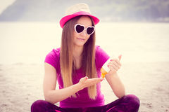 Happy girl in straw hat and sunglasses using sun lotion, sun protection on beach Royalty Free Stock Photography