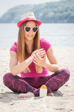 Happy girl in straw hat and sunglasses using sun lotion, sun protection on beach Royalty Free Stock Image