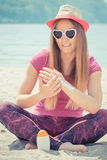 Happy girl in straw hat and sunglasses using sun lotion, sun protection on beach Stock Photos
