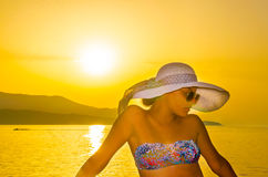 Happy girl with straw hat at sunset Royalty Free Stock Photography