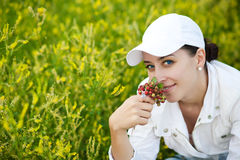 Happy girl with strawberries on a green meadow Royalty Free Stock Photo