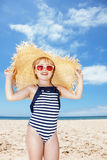 Happy girl in striped swimsuit and big straw hat on white beach Royalty Free Stock Photos