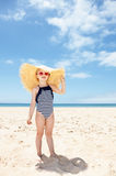 Happy girl in striped swimsuit and big straw hat on white beach Royalty Free Stock Image