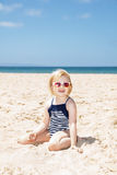 Happy girl in striped swimsuit playing with sand on white beach Royalty Free Stock Photography