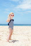 Happy girl in striped swimsuit on a white beach handwaving Stock Images
