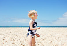 Happy girl in striped swimsuit on a white beach looking aside Royalty Free Stock Photo
