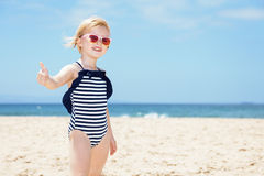 Happy girl in striped swimsuit on white beach showing thumbs up Royalty Free Stock Photography