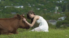Happy Girl Strokes A Cow At Summer Day. 4k Happy girl strokes brown cow in the green pasture at summer day stock footage