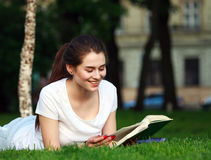 Happy girl student in city park reading a book Stock Image