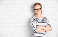 Happy  girl student in glasses at a blank white brick wall Stock Photo