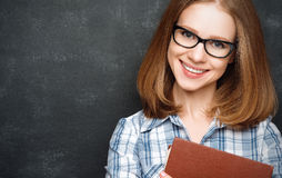 Happy girl student with glasses and book from blackboard stock photos