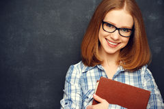 Happy girl student with glasses and book from blackboard Stock Photo