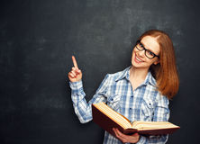 Happy girl student with glasses and book from blank blackboard Stock Photo
