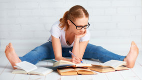 Happy girl student preparing homework, preparing for the exam wi. Th books at home on the floor stock images