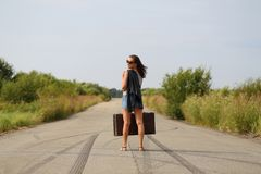 Happy girl with a suitcase on the road Stock Image