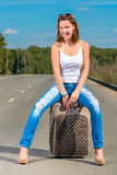 Happy girl with a suitcase on the road Stock Photography