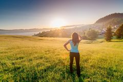 Happy girl at summer meadow enjoying beauty morning in mountains. And celebrating new day. Female enjoying life at sunny morning. Happy young woman at mountains Stock Photo