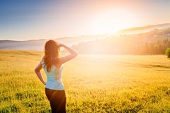 Happy girl at summer meadow enjoying beauty morning in mountains. And celebrating new day. Female enjoying life at sunny morning. Happy young woman at mountains Royalty Free Stock Image