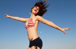Happy girl summer sky swimsuit. Beautiful happy girl summer sky jumping in swimsuit royalty free stock image