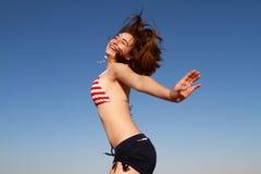 Happy girl summer sky swimsuit. Beautiful happy girl summer sky jumping in swimsuit royalty free stock photo