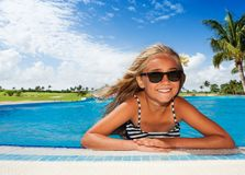 Happy girl sunbathing in the outdoor swimming pool Royalty Free Stock Images